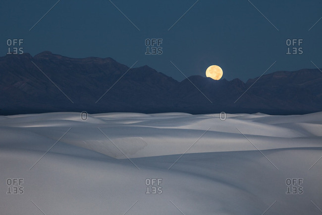Full moon setting at dawn behind San Andres Mountains near White Sands National Monument
