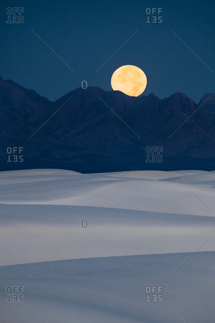 Full moon setting at dawn behind San Andres Mountains near White Sands National Monument, New Mexico