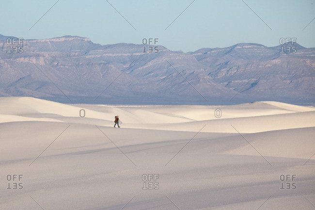 Man walking with a tripod on dunes in White Sands National Monument