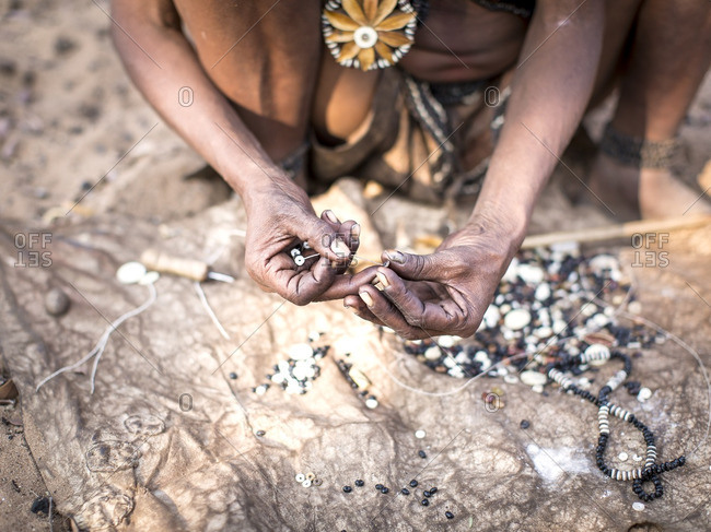 Namibia - July 19, 2015: A portrait of a San tribesman hand making traditional bead jewelry