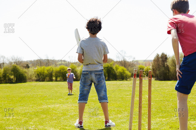 Boys playing cricket on field