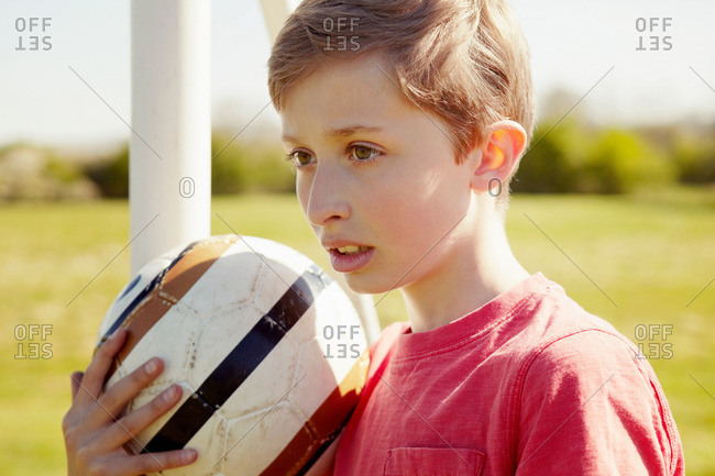 Boy with ball looking into the distance