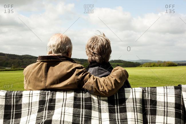 Back view of senior couple enjoying scenery on field