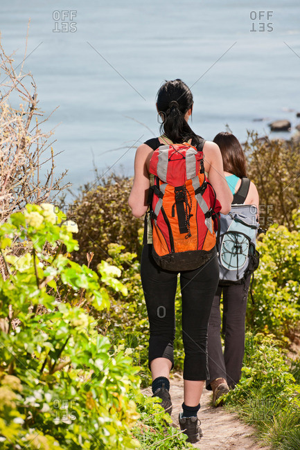 Two female friends walking down coastal path