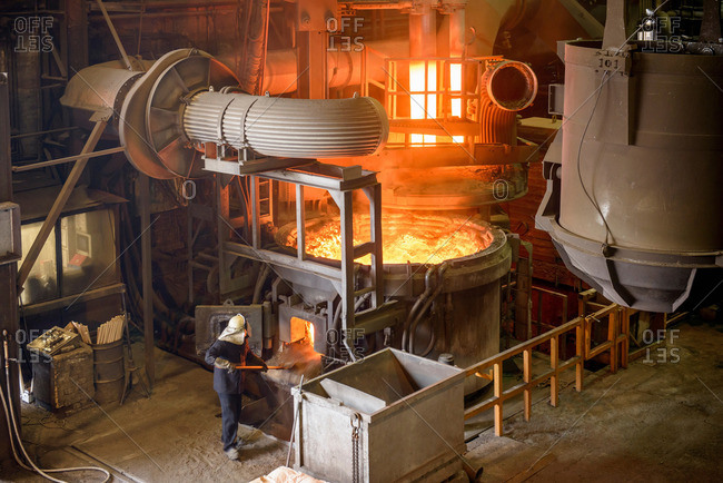 Steel worker working at an open electric steel furnace in an industrial foundry
