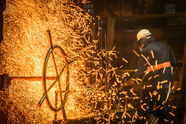 Steel worker next to sparks from molten steel in industrial foundry