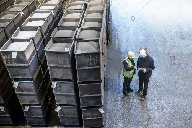 Steel workers in industrial steel foundry inspecting paperwork next to crates of steel shot, high angle view