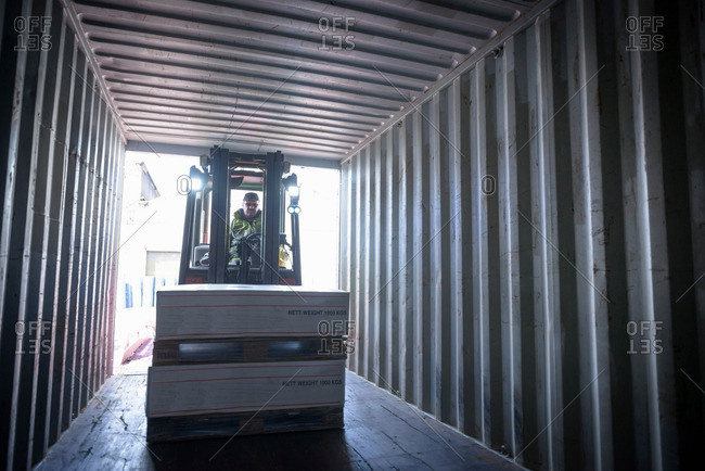 Forklift truck loading products into shipping container