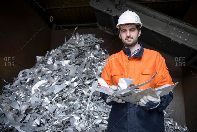 Worker inspecting aluminum scrap in aluminum recycling plant, portrait