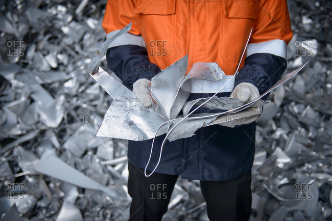 Worker holding aluminum scrap in aluminum recycling plant, close up