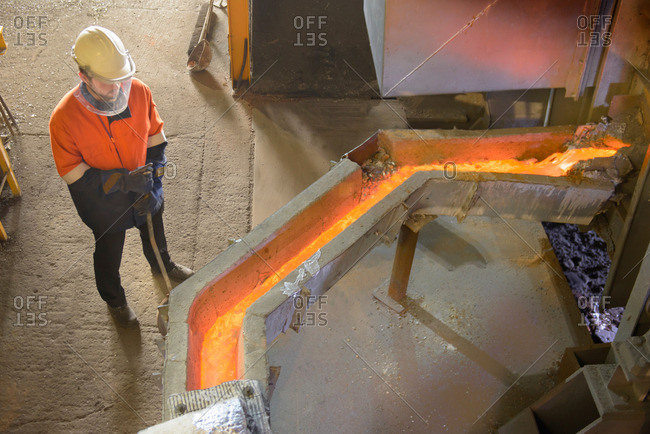 Worker watching molten aluminum in aluminum foundry, high angle view