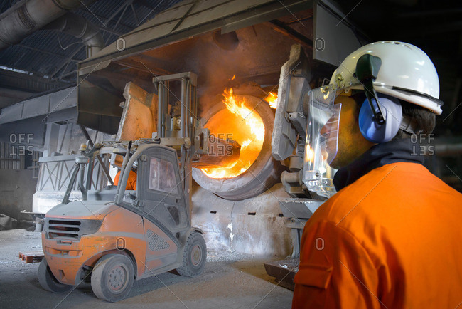 Worker in protective clothing watching forklift truck at furnace in aluminum foundry