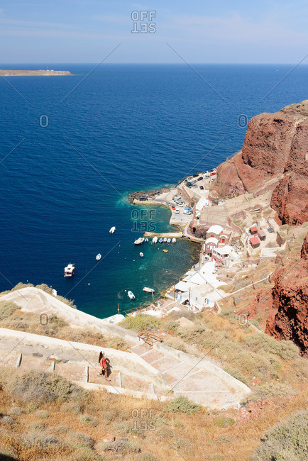 Distant view of female tourist walking down steps, Oia, Santorini, Greece