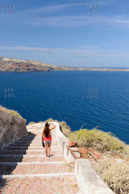 Female tourist walking down steps, Oia, Santorini, Greece