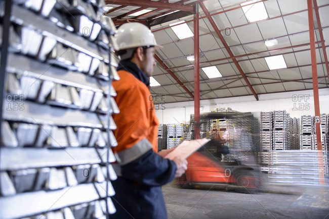 Worker watching forklift truck carrying aluminum ingots in warehouse, blurred motion