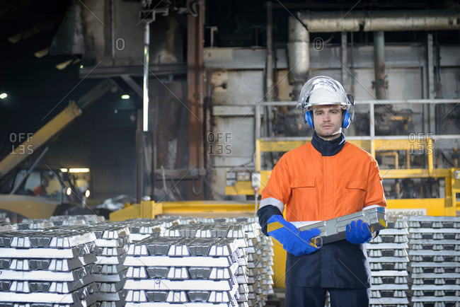 Worker in protective work wear carrying aluminum ingot in foundry