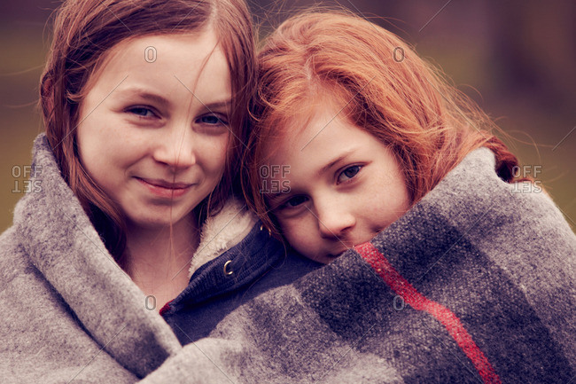 Portrait of girls wrapped in a blanket outdoors