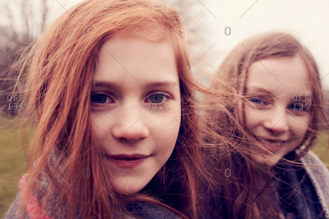 Portrait of girls wrapped in a blanket outdoors, smiling
