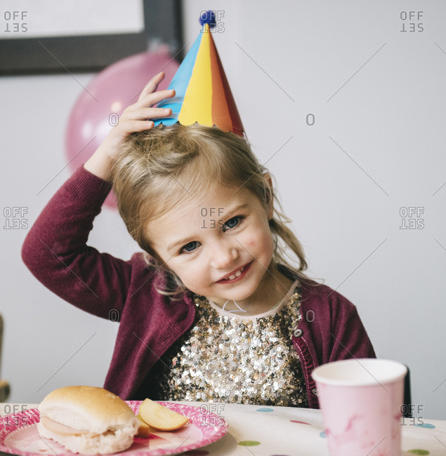 A young girl in a party hat at a birthday party
