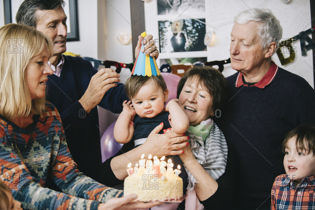 A family gathered to celebrate a one year old girl\'s birthday party A cake with lots of candles