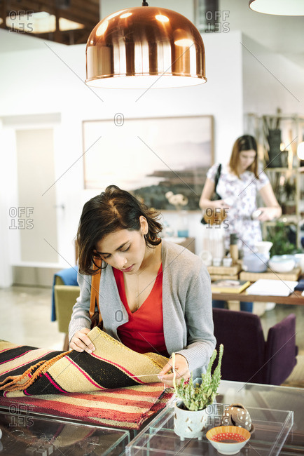 Young woman in a shop, looking at small striped rugs
