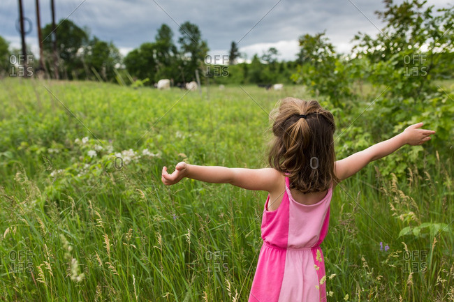 Girl standing in a field with her arms outstretched