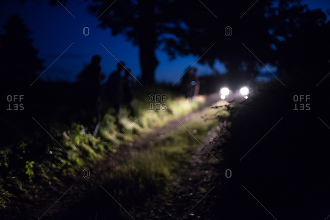 Headlights from an oncoming car illuminating a narrow rural road