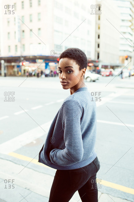 Portrait of a woman walking down a city street looking back over her shoulder