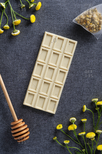 Chocolate bar surrounded by wildflowers, sachet, and honey drizzler
