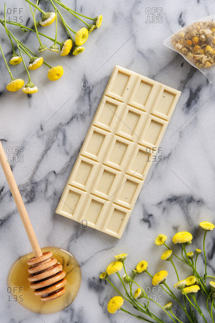 Chocolate bar surrounded by wildflowers, sachet, and honey drizzler on a marble table