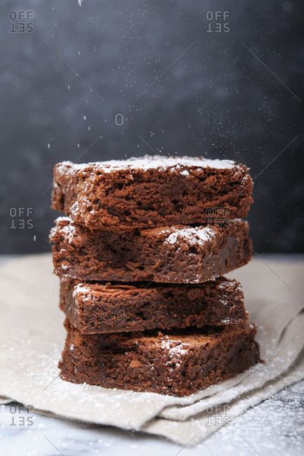 A stack of brownies being dusted with confectioners sugar