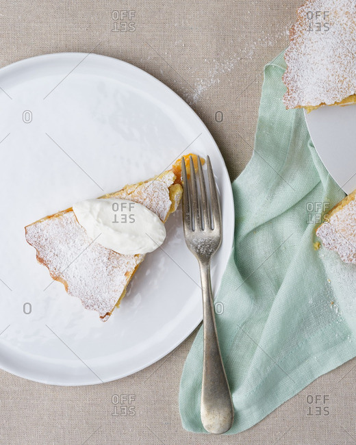 A slice of apricot frangipane served with fresh whipping cream