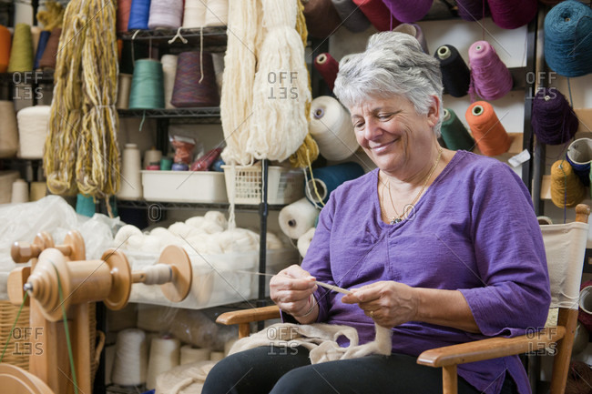 Senior woman handspinning wool into yarn at a fiber arts studio