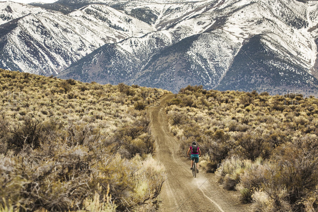 MONO LAKE, CA, USA A young woman rides a mountain bike down a dirt road with snow-covered mountains in the distance
