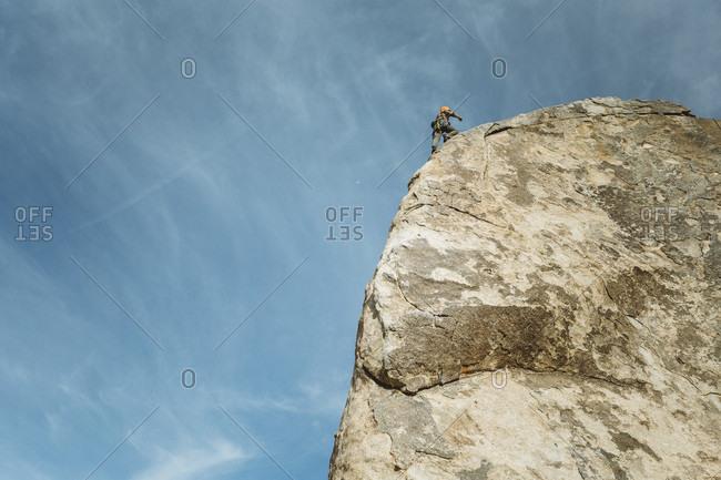 A man climbing Headstone Rock in Joshua Tree, CA