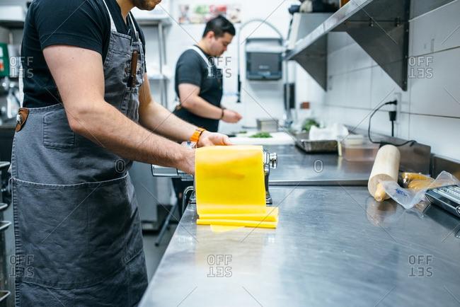 Chef pressing dough for pasta in a machine