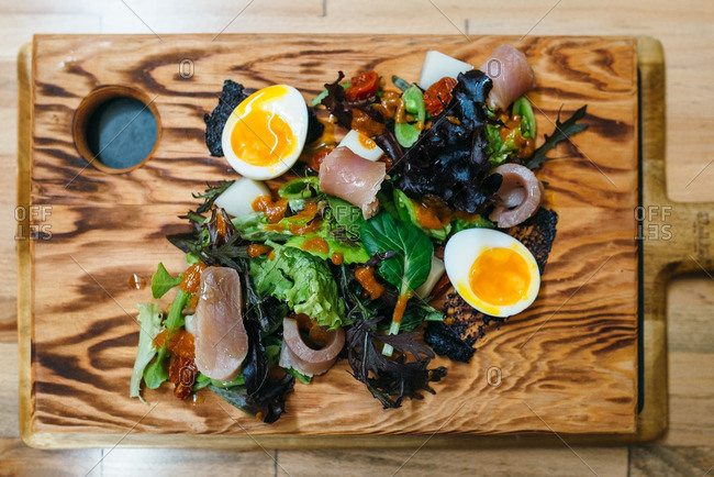 Overhead view of salad with tuna and soft boiled eggs on a cutting board