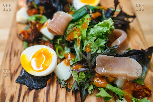 Salad with tuna and soft boiled eggs on a cutting board