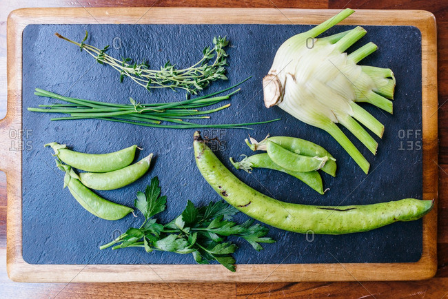 Green vegetables on a slate cutting board