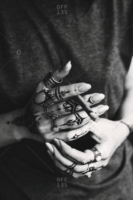 Female hands with henna tattoos holding a black cigarette