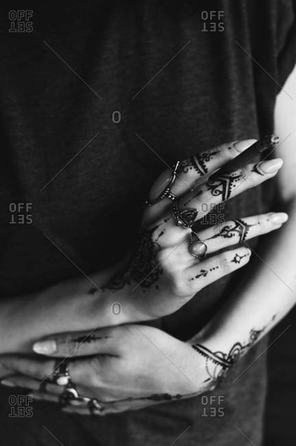 Hands with folk rings and henna tattoos holding a black cigarette