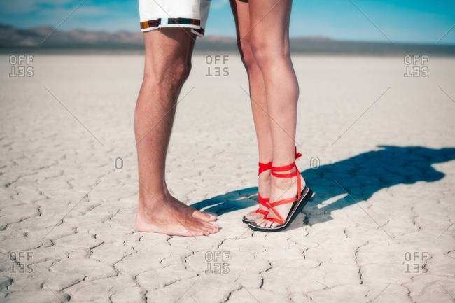 Feet of a couple standing in the desert