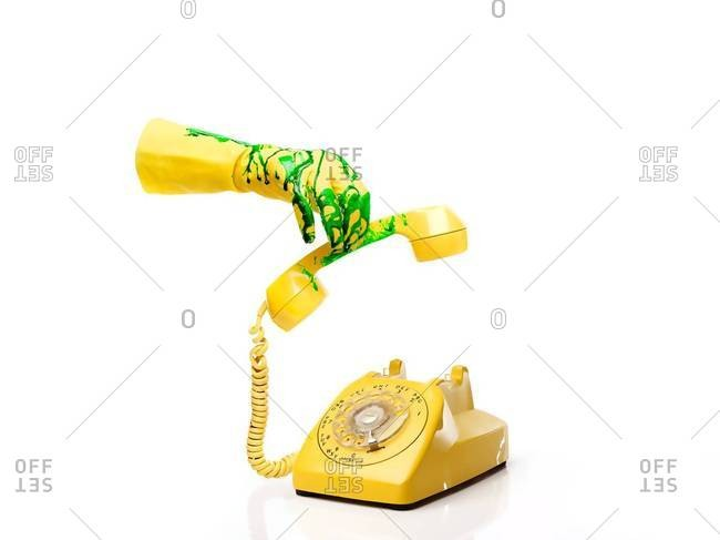 Rubber glove covered in green slime picking up handset of telephone