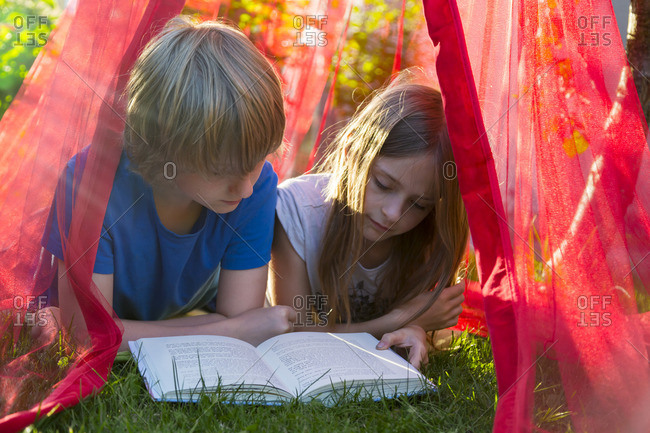 Sister and brother lying on a meadow under mosquito net reading a book together