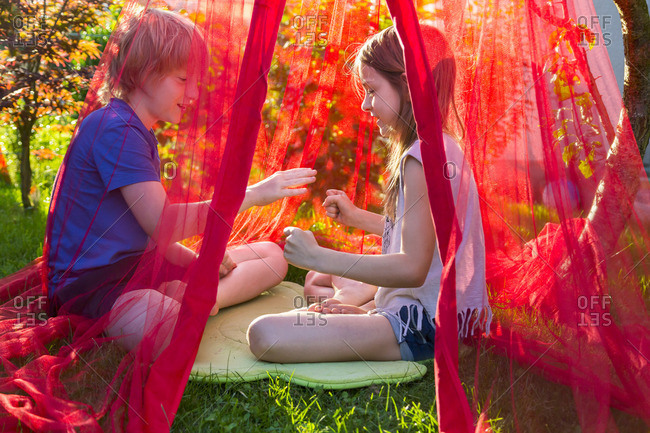 Sister and brother sitting in the garden under mosquito net playing Scissors Paper Stone