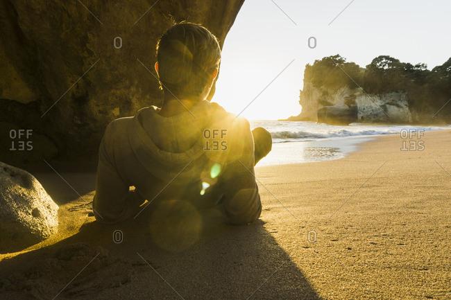 New Zealand- Wanganui- back view of man lying on the beach watching sunrise
