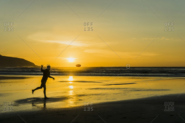Silhouette of man on the beach playing with plastic disc at twilight