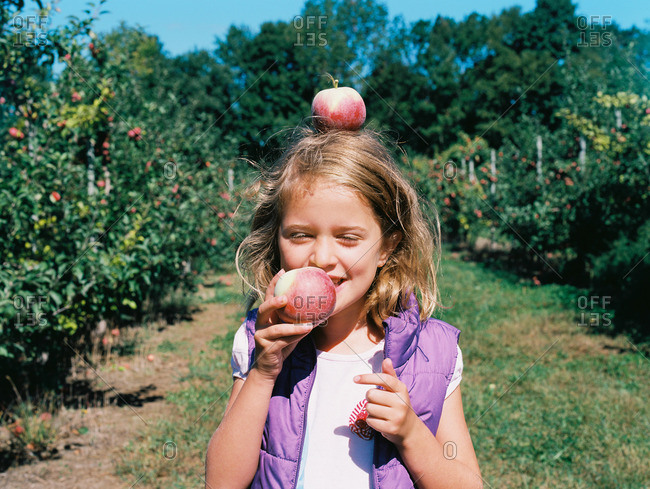 Girl eating an apple and balancing one on her head