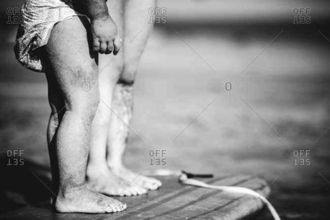 Close up of two children's legs on the beach