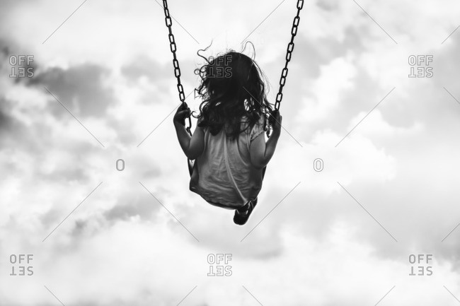 Low angle view of a little girl on a swing